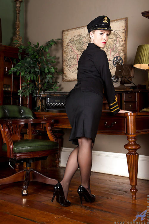 Older blonde stewardess Evey Crystal posing in stockings and high heels